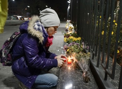 A Ukrainian woman lights a candle to pay tribute to victims of the crash,