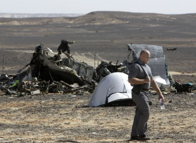 A Russian investigator walks near wreckage a day after a passenger jet bound for St Petersburg crashed in Hassana, Egypt.