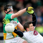 Kildare's Eamonn Callaghan and Offaly's masked man Eoin Rigney.<span class=