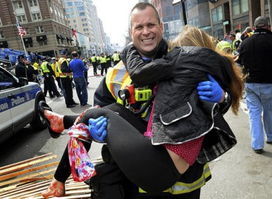 Boston Firefighter James Plourde carries Victoria McGrath from the scene after a bombing near the Boston Marathon finish line.