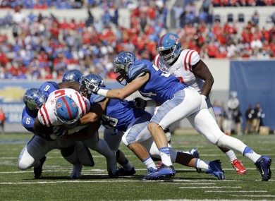 Mississippi defensive tackle Robert Nkemdiche (5) is brought down by Memphis defenders as Nkemdiche runs the ball on an offensive play in the first half of an NCAA college football game last year. He suffered a concussion on the play.