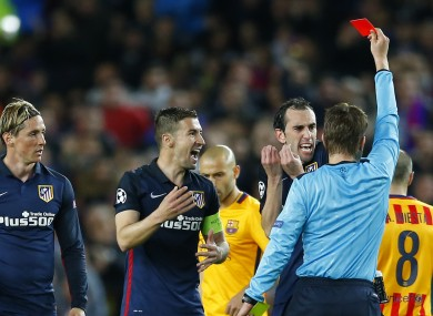 Referee Felix Brych turns away after showing a red card to Atletico's Fernando Torres.