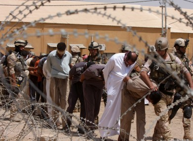 File photo of suspected al-Qaida members being led away to detention centers in Iraq.
