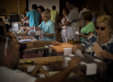 A woman casts her vote for the national elections in Barcelona, Spain.