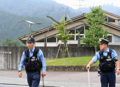Police officers stand guard a facility for the disabled where a number of people were killed and dozens injured in a knife attack.