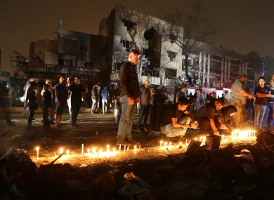 People light candles at the scene of a massive car bomb attack in Karada