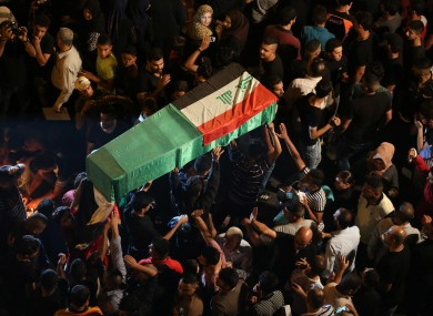 Mourners carry the Iraqi flag-draped coffin of a bomb victim during a funeral procession in the bustling commercial district of Karada, Baghdad