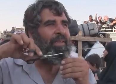 Man cuts beard during celebrations on the street.