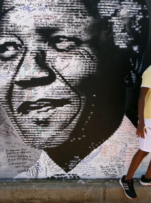 A young boy stands in front of a poster of former South African president Nelson Mandela.