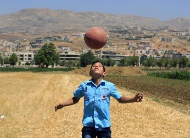 Syrian schoolchild Mouhannad al-Jassem, 11, who fled with his family from Idlib, plays soccer at a refugee camp in Saadnayel, in the Bekaa Valley in Lebanon.