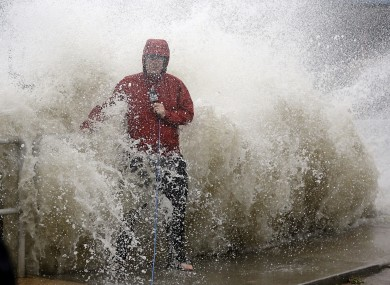 A news reporter doing a stand up near a sea wall in Cedar Key, Florida, is covered by an unexpected wave.