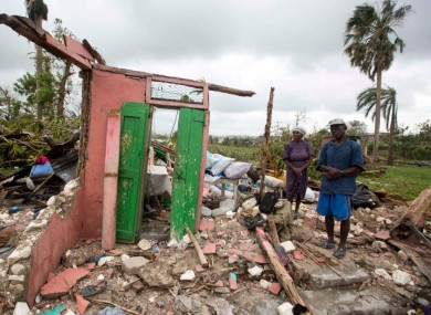 Saintanor Dutervil stands with his wife in the ruins of their home destroyed by Hurricane Matthew in Haiti.