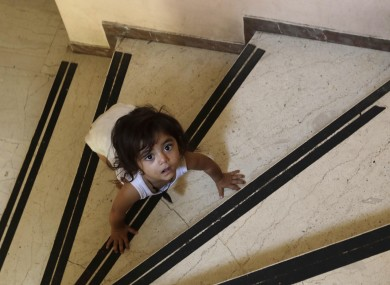 A child crawls on the steps of an abandoned hospital wing, used as a makeshift shelter for around 150 Syrian refugees, in Athens.