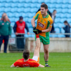 Corofin's Ian Burke helps out Castlebar Mitchels Donie Newcombe.<span class=