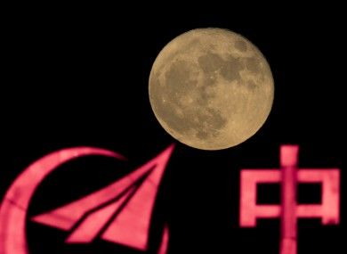 The logo for AVIC, or Aviation Industry Corp, silhouetted on front of a supermoon.