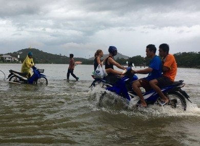 Riders use a road flooded by an overflowing lake on Ko Samui in Thailand yesterday.