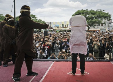 A Shariah law official whips one of two men convicted of gay sex during a public caning outside a mosque in Banda Aceh, Aceh province Indonesia.