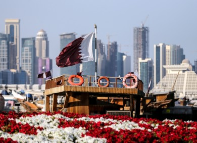 The Qatari flag waves in front of the capital, Doha.