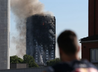 A man watches smoke pouring from a fire that has engulfed the 27-storey Grenfell Tower in west London.