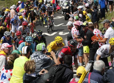 Britain's Chris Froome, wearing the overall leader's yellow jersey, is followed by Denmark's Jakob Fuglsang, Australia's Richie Porte, Colombia's Nairo Quintana, and Ireland's Daniel Martin, far left in blue and yellow, as he climbs towards Grand Colombier pass during the ninth stage of the Tour de France cycling race.