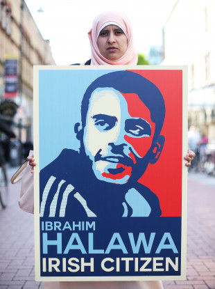 Somaia Halawa, sister of Ibrahim, holds a poster bearing her brother's face. ,