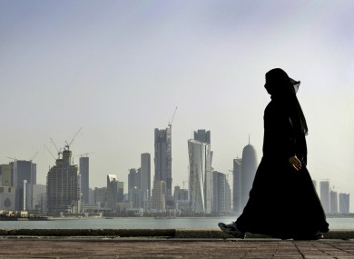 A Qatari woman walks in front of Doha, the capital city of Qatar.