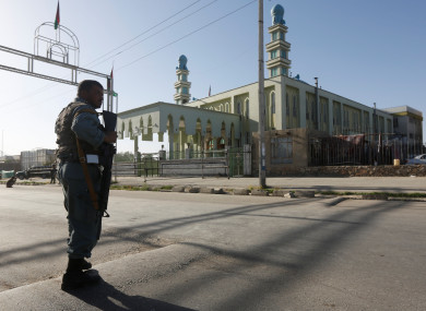 An Afghan policeman stands guard outside a mosque where a suicide bomber detonated a bomb, in Kabul, Afghanistan last week.