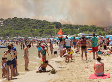 Beach goers watch as fires rage in Bormes-les-Mimosas, south-east France