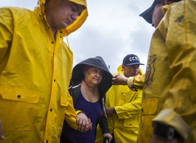 Corpus Christi firefighters help Guadalupe Guerra walk to a bus headed for San Antonio at an evacuation center