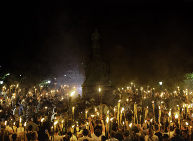 (File photo) White supremacists encircle counter protesters at the base of a statue of Thomas Jefferson after marching through the University of Virginia campus with torches in Charlottesville earlier this month.