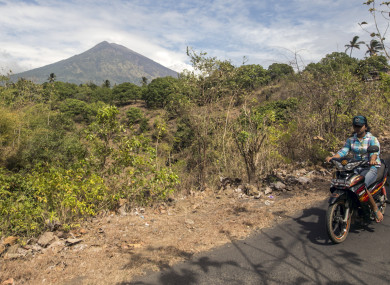 A villager rides past by with Mount Agung seen in the background in Karangasem, Bali, Indonesia.