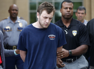 Kenneth James Gleason is escorted by police to a waiting police car in Baton Rouge.