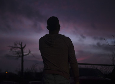 man looks at the horizon early in the morning after the passing of Hurricane Maria.