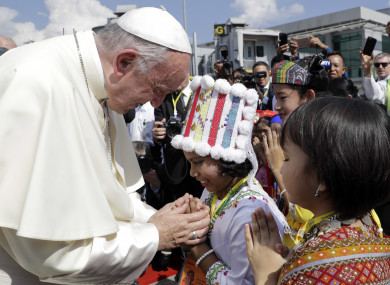 Pope Francis is greeted by young children in traditional clothes upon his arrival at Yangon's airport, Myanmar.