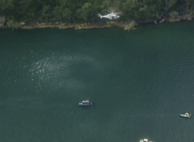 A search and rescue helicopter flies above search boats in Hawkesbury River, New South Wales, Australia