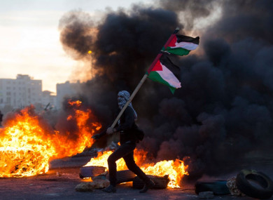 A Palestinian protester pictured yesterday during clashes with Israeli troops following protests against Trump's decision
