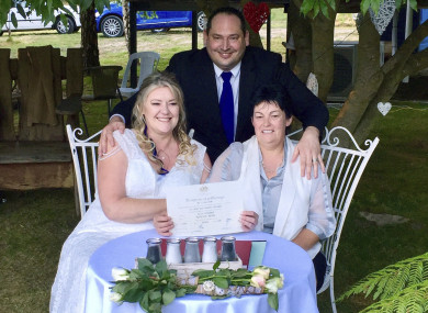 Lainey Carmichael, left, Roz Kitschke, right, and celebrant Jason Betts pose as they show Lainey and Roz's marriage certificate at their home in Franklin, south of Hobart, Australia.