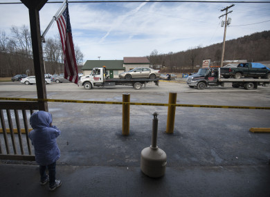 A little girl watches from the front of G&D Market as trucks remove three vehicles from the scene.