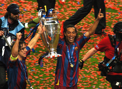 Ronaldinho lifting the Champions League trophy with Barcelona captain Carles Puyol in 2006.