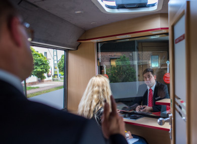 File photo of a bank worker serving customers inside a bus used by the German Sparkasse bank as a mobile local branch parked in Bornsdorf, Germany.