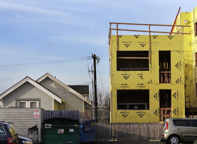 A four-storey mixed-use building is under construction adjacent to an older, single-family home in Seattle.
