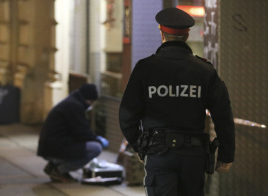 A police officer passes by a forensic expert after several people have been injured in a knife attack on the streets of Vienna