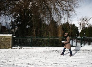 A woman walking through Glasnevin in Dublin during the snow.