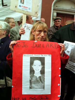 Mary Phelan holding a poster of her sister in 1997.