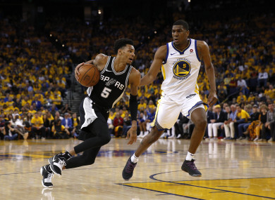 Dejounte Murray dribbles past Golden State Warriors forward Kevon Looney.