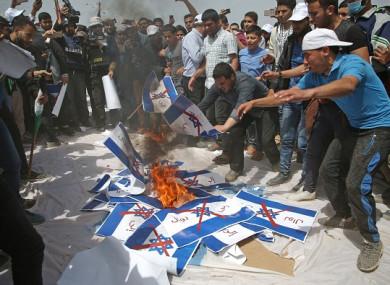 Palestinians burn Israeli flags on Friday.