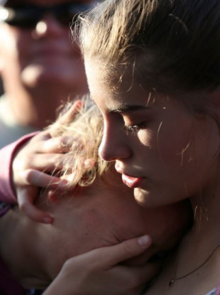 Abigail Adams, right, comforts her friend Hannah Hershey during a vigil for the victims of the Santa Fe High School shooting on Friday.