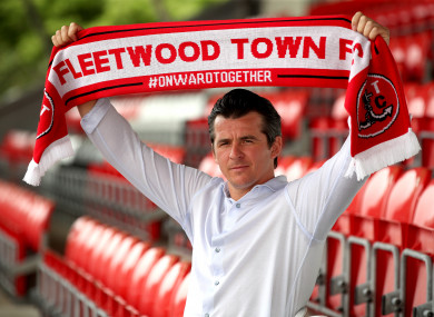 New Fleetwood Town manager Joey Barton holds up a scarf after the press conference at Highbury Stadium.