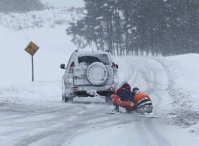 Two people on a makeshift snowboard are towed behind a jeep on the R413 road through the Curragh in County Kildare during Storm Emma earlier this year.