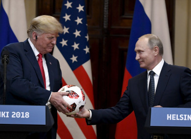 Russian President Vladimir Putin presents a football to US President Donald Trump.
